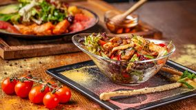 The concept of Indian cuisine. Warm salad with beef and chicken, bell pepper and honey mint sauce. Serving dishes in a restaurant stock photography