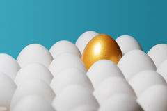 The concept of individuality, exclusivity, better choice. One golden egg among white eggs on blue background stock image