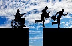 Concept of inequality and discrimination of people with disabilities. The silhouette of a disabled worker in a wheelchair stopped before an abyss and healthy stock images