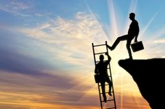 Concept of inequality and injustice. Silhouette of a businessman climbs up the stairs and another businessman pushes this ladder. The concept of inequality and stock photography