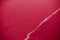 Concept of infidelity or fragile/fugitive/ephemeral love: heart. Drawn in sand being washed by the sea Stock Photography