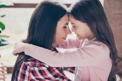 Concept of infinite love between the closest relatives. Close up. Photo of happy calm and joyful mother and her daughter with long beautiful hair, they are royalty free stock images