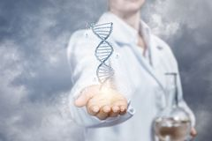 The concept is the innovations in DNA researches. A laboratory assistant is showing a DNA model in one hand and holding a flask with transparent substance in an royalty free stock photos
