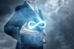 The concept is the innovative idea boundless. A businesswoman is holding the infinity sign against the fog background. The concept is the innovative idea stock photography