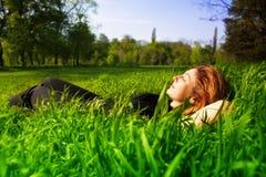 Concept insousiant - détente de femme extérieure dans l'herbe photo libre de droits