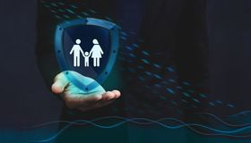 Concept For Insurance Company to Safe and Supporting Customer, F. Amily icon inside a Shield Guard to Protected them from Rain and Flood over a Businessman Hand Stock Photos