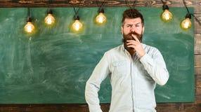 Concept intellectuel de tâche L'homme avec la barbe et la moustache sur le visage réfléchi se tiennent devant le tableau Hippie b photo libre de droits