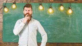 Concept intellectuel de tâche L'homme avec la barbe et la moustache sur le visage réfléchi se tiennent devant le tableau Hippie b photo stock