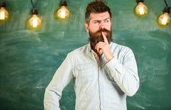 Concept intellectuel de tâche L'homme avec la barbe et la moustache sur le visage réfléchi se tiennent devant le tableau Pensée d photo stock
