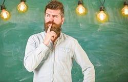 Concept intellectuel de tâche L'homme avec la barbe et la moustache sur le visage réfléchi se tiennent devant le tableau Pensée d photos libres de droits
