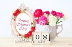 Concept international de jour de femmes avec de belles fleurs pendant le vase et la date sur la table en bois Photos stock