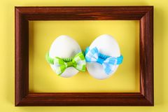 The concept for the international friendship day. Eggs in bows on a yellow pastel background. The concept for the international friendship day. Eggs in bows on stock photo
