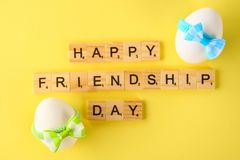 The concept for the international friendship day. Text and eggs in bows on a yellow pastel background. The concept for the international friendship day. Text royalty free stock photos