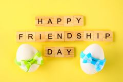 The concept for the international friendship day. Text and eggs in bows on a yellow pastel background. The concept for the international friendship day. Text royalty free stock photography