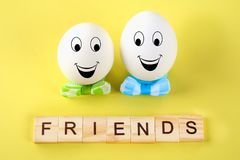 The concept for the international friendship day. Text and eggs. In bows on a yellow pastel background stock images