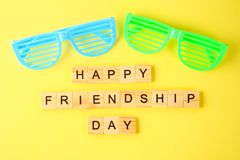 The concept for the international friendship day. Text and glass. Es on a yellow pastel background stock images
