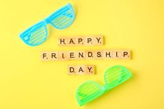 The concept for the international friendship day. Text and glasses on a yellow pastel background. The concept for the international friendship day. Text and royalty free stock photo