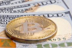 The concept of investment, wealth and the exchange of crypto-currencies. Virtual coin of gold bitcoin on the background of hundred. Virtual coin of gold bitcoin Royalty Free Stock Photo