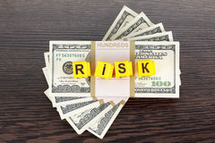 Concept investments risk, word made by letter, stack of dollar bills Stock Photography