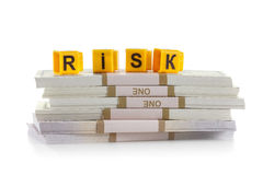 Concept investments risk, word made by letter, stack of dollar bills Royalty Free Stock Photography