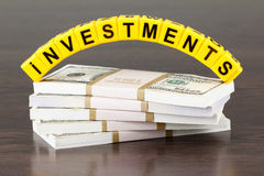 Concept investments, word made by letter, stack of dollar bills Royalty Free Stock Image