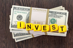 Concept investments, word made by letter, stack of dollar bills Stock Photo