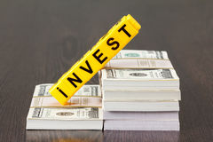 Concept investments, word made by letter, stack of dollar bills Stock Photos