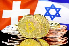 Bitcoins on Switzerland and Israel flag background. Concept for investors in cryptocurrency and Blockchain technology in the Switzerland and Israel. Bitcoins on stock photo