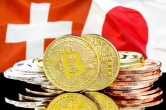Bitcoins on Switzerland and Japan flag background. Concept for investors in cryptocurrency and Blockchain technology in the Switzerland and Japan. Bitcoins on royalty free stock image