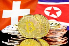 Bitcoins on Switzerland and North Korea flag background. Concept for investors in cryptocurrency and Blockchain technology in the Switzerland and North Korea stock image