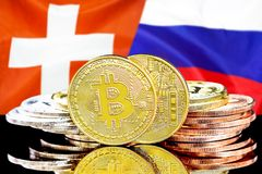 Bitcoins on Switzerland and Russia flag background. Concept for investors in cryptocurrency and Blockchain technology in the Switzerland and Russia. Bitcoins on stock image