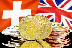 Bitcoins on Switzerland and UK flag background. Concept for investors in cryptocurrency and Blockchain technology in the Switzerland and United Kingdom. Bitcoins stock photography