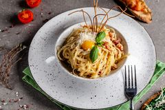 The concept of Italian cuisine. Pasta carbonara with bacon, parmesan and egg yolk. The decor of fried spaghetti. Serving dishes. In a restaurant in a white stock photo