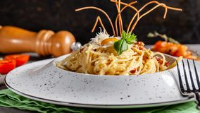 The concept of Italian cuisine. Pasta carbonara with bacon, parmesan and egg yolk. The decor of fried spaghetti. Serving dishes. In a restaurant in a white royalty free stock image