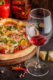Concept Italian cuisine. A real pizza with vegetables and ham, bacon and parmesan cheese. The ingredients on the table. Red wine. In a glass on the table stock images