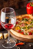Concept Italian cuisine. A real pizza with vegetables and ham, bacon and parmesan cheese. The ingredients on the table. Red wine. In a glass on the table stock image