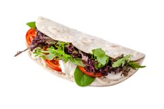 The concept of Italian cuisine. Vegatarian piadina with tomatoes, mozzarella cheese, mix lettuce, arugula and sauce on white. The concept of Italian cuisine royalty free stock image