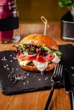 Concept of Italian home cooking. Burger with beef and pork meat cutlet, mozzarella cheese, salami sausage, parma, arugula. And lettuce mix. Beautiful serving in stock photo