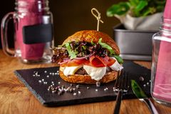 Concept of Italian home cooking. Burger with beef and pork meat cutlet, mozzarella cheese, salami sausage, parma, arugula. And lettuce mix. Beautiful serving in stock image