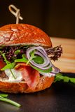 Concept of Italian home cooking. Burger with beef and pork meat cutlet, mozzarella cheese, salami sausage, parma, arugula. And lettuce mix. Beautiful serving in royalty free stock photography