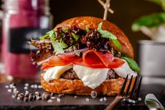 Concept of Italian home cooking. Burger with beef and pork meat cutlet, mozzarella cheese, salami sausage, parma, arugula. And lettuce mix. Beautiful serving in royalty free stock photos