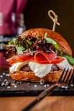 Concept of Italian home cooking. Burger with beef and pork meat cutlet, mozzarella cheese, salami sausage, parma, arugula. And lettuce mix. Beautiful serving in stock photography