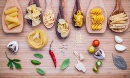 Concept italien de nourriture Divers genre de pâtes dans l'esprit en bois de cuillères Photographie stock libre de droits