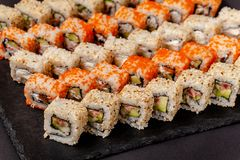 The concept of Japanese and Chinese cuisine. Set from sushi and rolls lie on a stone blackboard stock image