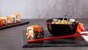 The concept of Japanese cuisine. Japanese lunch of noodles, sushi with shrimp, red caviar, eel, tuna. Soy sauce and red chinese. Sticks. background image. Top stock images