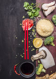 Concept of Japanese food rice with oyster mushrooms and squid, red chopsticks with cilantro and lemon on wooden rustic background Stock Photography