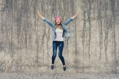 Concept of joy and freedom, life without problems. Crazy, extremely happy girl in jeans clothes and pink hat screaming and jumpin royalty free stock photos