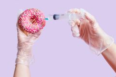Concept junk food. Hands, syringe and pink donut stock photo