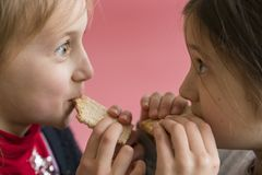 concept kids fighting for food. girls bite one slice of bread. Food shortage concept stock photography