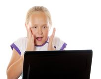 Concept of kids usind unsafe internet surfing. Surprised or scared girl surfing in internet, over white background Royalty Free Stock Images